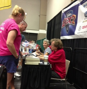 Bill Rodgers, Joan Samuelson & Meb Keflizighi (hidden) sign autographs at Bix Expo