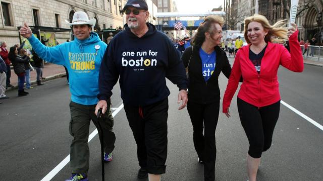 Carlos Arredondo, left, John Odom, his wife, Karen Odom, and Heather Abbott walk through Copley Square after crossing the Boston Marathon finish line during the One Run for Boston, Sunday, April 13, 2014.