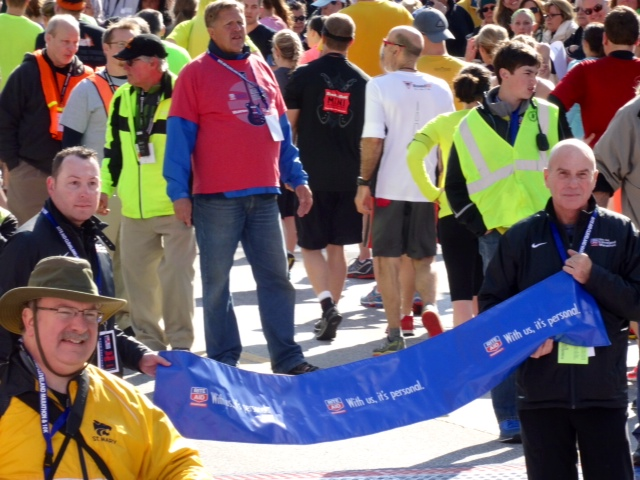 Running USA CEO Rich Harshbarger (left) holds finish line tape with Cleveland exec. director Jack Staph