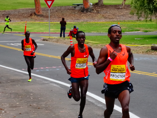 Mammoth TC's Gabe Proctor (eventual 9th - 61:39) presses Kenya's Cybrian Kotut (7th - 1:01:38) with USA's Shadrack Biwott coming strong ( 6th - 1:01:24)