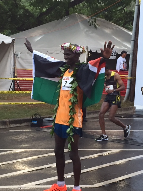 Champion's pose as fifth-place finisher and pre-race co-favorite Yemane Adhane of Ethiopia suffers in the background.